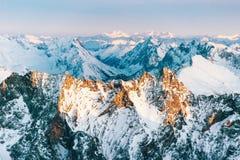 Vista aerea delle creste nevose della montagna rocciosa nel tramonto Immagine Stock Libera da Diritti