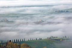 Vista aerea delle fattorie della sommità & degli alberi di cipresso in Toscana su una mattina nebbiosa della molla ~ Immagine Stock