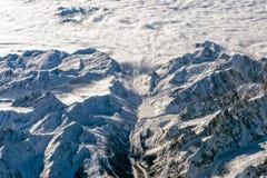 Vista aerea delle montagne delle alpi dalla neve e dalle valanghe dell'aeroplano Immagine Stock