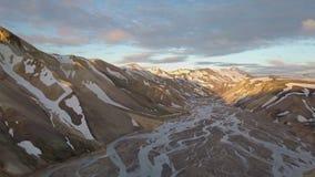 Vista aerea delle montagne nevose dell'arcobaleno islandese con il delta del fiume nella sera di tramonto archivi video