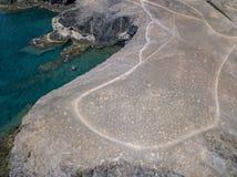 Vista aerea delle rive e delle spiagge dentellate di Lanzarote, Spagna, canarino Battello pneumatico rosso attraccato in una baia fotografia stock libera da diritti