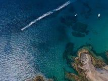 Vista aerea delle rive e delle spiagge dentellate di Lanzarote, Spagna, canarino Il battello pneumatico rosso traversa seguito da fotografie stock