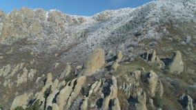 Vista aerea delle rocce enormi su una collina della montagna coperta dagli arbusti e dagli alberi nevosi contro cielo blu colpo P stock footage