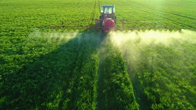 Vista aerea di alba del trattore agricolo che ara e che spruzza sul campo archivi video