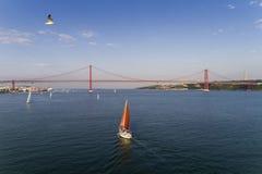 Vista aerea di bella barca a vela sul Tago con i 25 di April Bridge sui precedenti, nella città di Lisbona, porta Immagine Stock