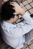 Vista aerea di giovane uomo asiatico depresso ansioso di affari che si siede e che tocca fronte con le mani immagine stock