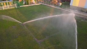 Vista aerea di innaffiatura del prato inglese di un campo di football americano stock footage