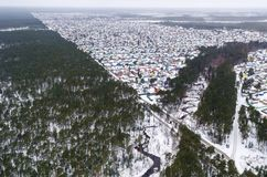 Vista aerea di inverno alta sopra poche case nella valle, circondata dalla foresta del pino Fotografia Stock