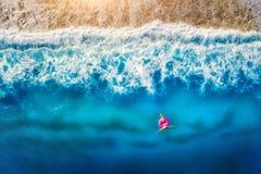 Vista aerea di nuoto della donna sull'anello rosa di nuotata nel mare immagini stock libere da diritti