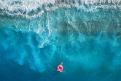 Vista aerea di nuoto della giovane donna sull'anello rosa di nuotata fotografia stock libera da diritti