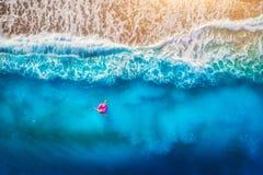 Vista aerea di nuoto della giovane donna sull'anello rosa di nuotata fotografia stock
