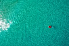 Vista aerea di nuoto esile della donna sulla ciambella dell'anello di nuotata nel mare trasparente del turchese in Seychelles Vis immagine stock libera da diritti