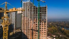 Vista aerea di paesaggio nella città con le costruzioni in costruzione e le gru industriali Mattoni che si situano all'aperto immagine stock