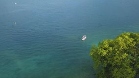 Vista aerea di piccola imbarcazione a motore che galleggia nell'acqua di mare del turchese vicino al grande albero verde azione S fotografia stock