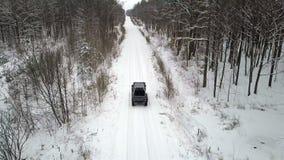 Vista aerea di SUV 6x6, guidante su una strada innevata nella foresta di inverno, vista posteriore video d archivio