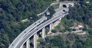 Vista aerea di traffico di automobili su un ponte stradale con l'entrata del tunnel della strada video d archivio