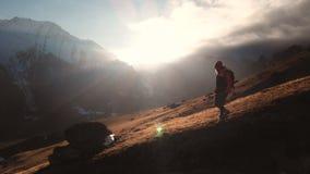 Vista aerea di un colpo epico di una ragazza che cammina sull'orlo di una montagna come siluetta in un bello tramonto archivi video