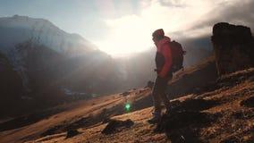 Vista aerea di un colpo epico di una ragazza che cammina sull'orlo di una montagna come siluetta in un bello tramonto video d archivio