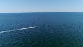 Vista aerea di un jet ski dell'acqua che guida in mare lontano da terra archivi video