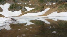 Vista aerea di un lago naturale alpino durante la stagione primaverile Fusione della neve Alpi italiane L'Italia stock footage