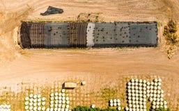Vista aerea di un magazzino dell'azienda agricola, verticale fotografato intorno alle balle del silaggio avvolte in stagnole Immagini Stock Libere da Diritti