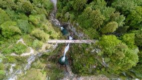 Vista aerea di un ponte pedonale attraverso una gola con una cascata, vista superiore fotografia stock