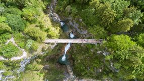 Vista aerea di un ponte pedonale attraverso una gola con una cascata, vista superiore fotografia stock libera da diritti