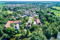 Vista aerea di un villaggio tedesco con una piccola foresta, uno stagno e un castello moated nella priorità alta Fotografie Stock Libere da Diritti