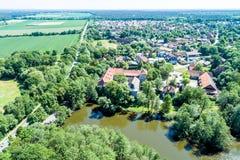 Vista aerea di un villaggio tedesco con una piccola foresta, uno stagno e un castello moated nella priorità alta Fotografia Stock