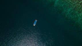 Vista aerea di una barca accanto ad una scogliera in mezzo al mare fotografia stock libera da diritti