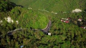 Vista aerea di una depressione curva della strada di avvolgimento le montagne con gli alberi verdi archivi video