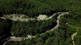 Vista aerea di una depressione curva della strada di avvolgimento le montagne archivi video