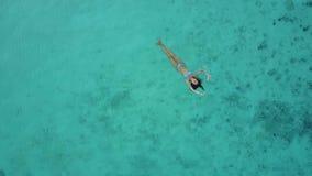 Vista aerea di una donna attraente in un bikini che galleggia nel mare cristallino Nuoto abbastanza bello della ragazza nell'indi stock footage