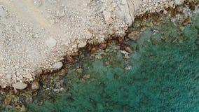 Vista aerea di una linea costiera della scogliera con le pietre e le onde del mare del turchese Video aereo verticale 4K video d archivio