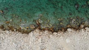 Vista aerea di una linea costiera della scogliera con le pietre e le onde del mare del turchese Video aereo verticale 4K archivi video