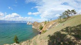 Vista aerea di una ragazza che si siede su una riva e su un disegno rocciosi Bello paesaggio stock footage