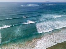 Vista aerea di una spiaggia, riva, onde che si schiantano sulla spiaggia di Famara della costa Lanzarote, Spagna immagini stock libere da diritti