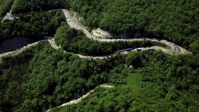 Vista aerea di una strada di bobina curva con il passaggio delle automobili stock footage