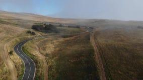 Vista aerea di una strada vuota fra le colline Strada con molte nuvole e nebbia archivi video