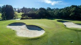 Vista aerea di verde del campo da golf con i bunker della sabbia il giorno soleggiato circondati dagli alberi Immagini Stock