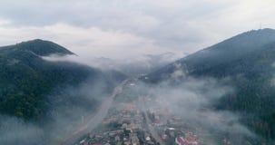 Vista aerea: Foresta nebbiosa, volante attraverso le nuvole in città Transcarpathian Mizhgirja video d archivio