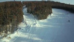 Vista aerea: Gli sciatori scendono il pendio stock footage