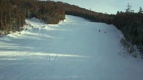 Vista aerea: Gli sciatori scendono il pendio archivi video