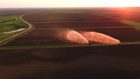 Vista aerea: Impianto di irrigazione che innaffia un campo dell'azienda agricola Fotografie Stock