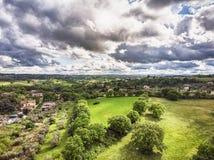 Vista aerea impressionante con le colline verdi, campi coltivare con gli alberi da frutto e prati e cielo scenico fotografia stock libera da diritti