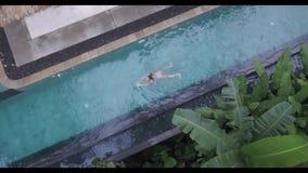 Vista aerea impressionante di nuoto della ragazza in uno stagno dell'aria aperta in hotel tropicale, stock footage