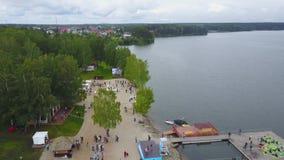 Vista aerea: Lago piacevole nella campagna Vista aerea della gente su una spiaggia sabbiosa nel lago È una vista colourful video d archivio