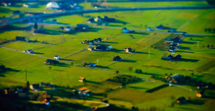 Vista aerea miniatura dello inclinazione-spostamento del villaggio in alpi Fotografia Stock Libera da Diritti