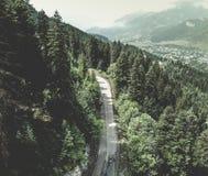 Vista aerea sopra la strada della montagna che passa attraverso il paesaggio della foresta Fotografia Stock