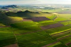 Vista aerea sopra una bella scena con i campi, i laghi e le montagne verdi all'ora dorata in primavera Immagini Stock Libere da Diritti